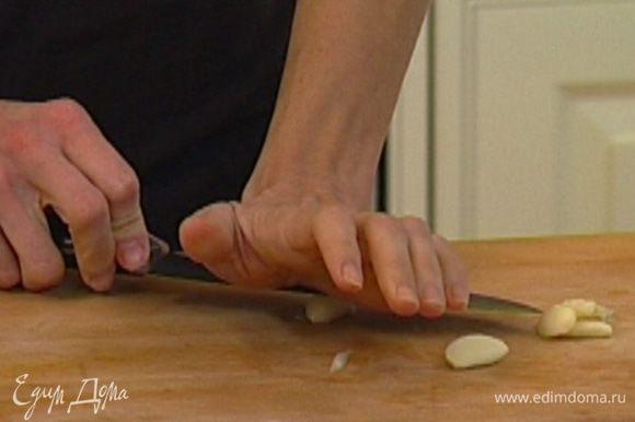 Чеснок почистить, раздавить плоской стороной ножа, добавить в кастрюлю с луком и все перемешать.