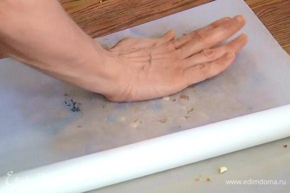 Поместить тесто между двумя листами пекарской бумаги и, прижимая руками, распределить в пласт.