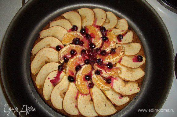 Достать пирог и украсить его тонко нарезанным яблоком, дольками мандарина и клюквой. Поставить снова в духовку на 10-15 минут. Готовый пирог немного остудить, посыпать сахарной пудрой перемешанной с корицей.