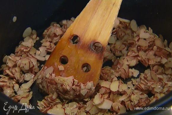 Приготовить нугу: хлопья миндаля подсушить в тяжелой кастрюле, добавить сахар и мед и прогреть, периодически помешивая.