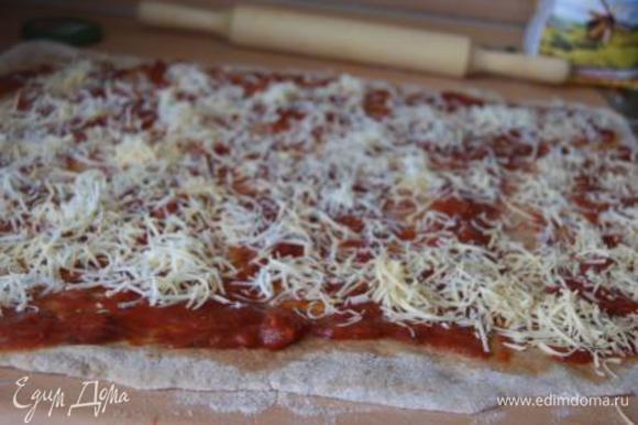 Тонким слоем распределить часть томатного соуса, присыпать сыром.