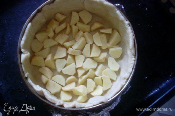 Отделить от теста 2/3 объема и раскатать круглую лепешку. Сложить лепешку в форму или сковороду для запекания, так, чтобы тесто доходило до краев бортиков. Разложить на дно половину объема картофеля.