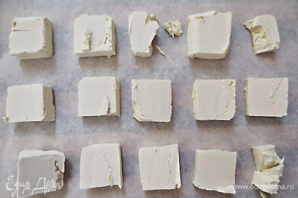 Масло разрезать на кусочки и выложить на бумагу для выпечки ( масло должно быть замороженным)