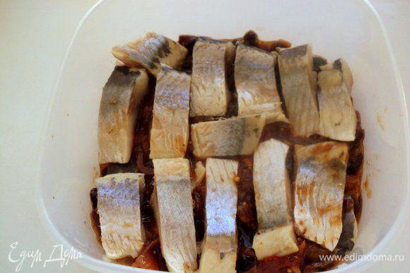 На дно судка выложить слой соуса, сверху кусочки сельди.