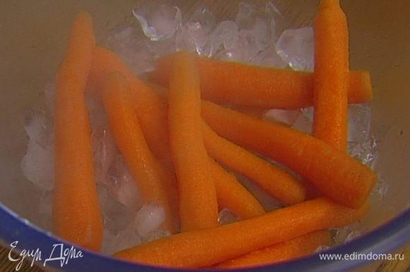 В отдельной кастрюле вскипятить воду, посолить и отправить туда морковь. Варить несколько минут и откинуть на сито, а затем поместить ее в лед. Охлажденную морковь обсушить бумажным полотенцем.