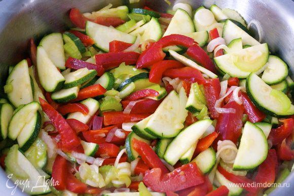 Нагреть духовку до 200 С. Разогреть оливковое масло в большой сковороде и обжарить сельдерей, красный перец, кабачок и зеленый лук на умеренном огне около 5 минут.