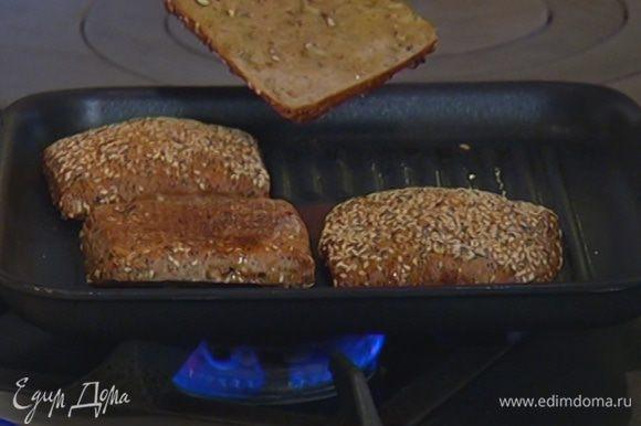 Разогреть сковороду-гриль и обжарить половинки булочек.