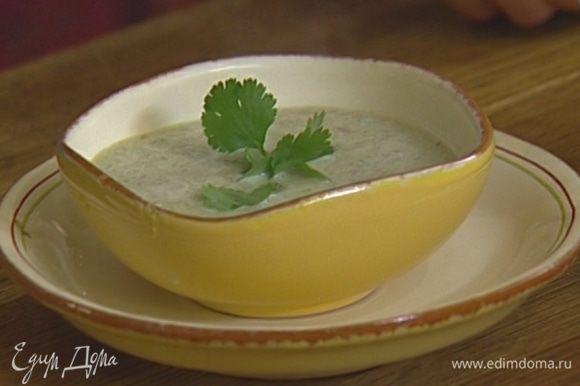 Готовый суп разлить по тарелкам и украсить листьями кинзы.