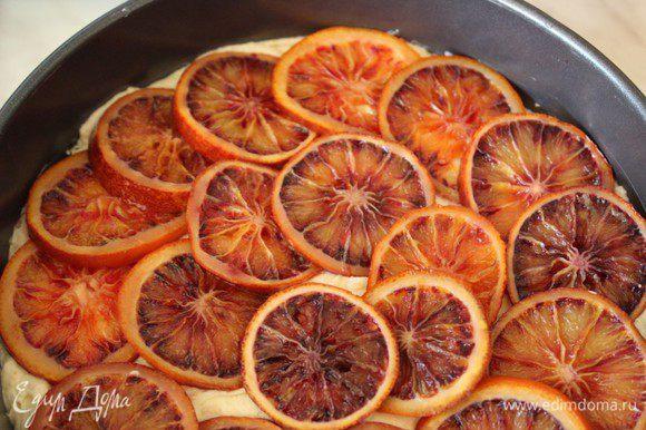 Выложить тесто в выстеленную пергаментом форму и разровнять. Выложить по всей поверхности кольца апельсинов. Выпекать в предварительно разогретой до 200 градусов духовке 15 минут. Затем снизить Т до 175 градусов и печь еще 30 минут. Готовность проверять при помощи деревянной шпажки.