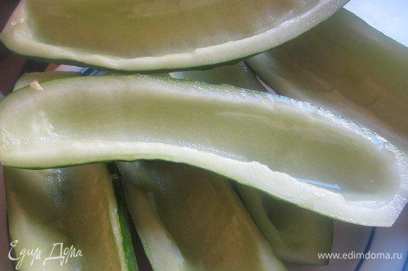 Огурцы лучше взять большие, их удобнее начинять. Срезать у огурцов конец со стеблем, разрезать вдоль и чайной ложкой выбрать сердцевину.