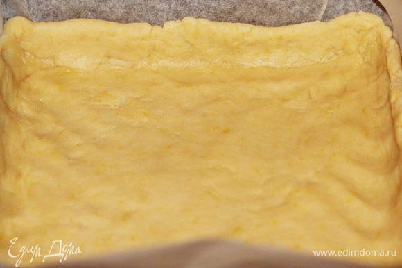Затем, постепенно добавляя воду, скатать тесто в мягкий эластичный шар. Раскатать тесто и выложить в противень, выстеленный пергаментом. Растянуть тесто по форме, сделав бортики, у меня приблизительно 2 см. Противень размером 20х20х5 см.
