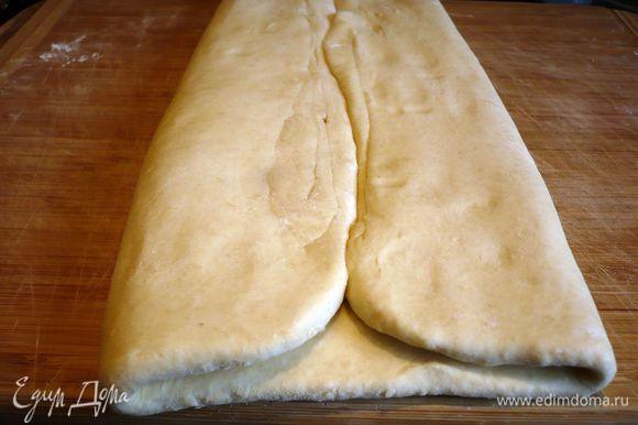Достаем тесто. Раскатываем его на присыпанной мукой поверхности. Теперь зрительно делим тесто на четыре равные части. Сворачиваем левый и правый края к середине.