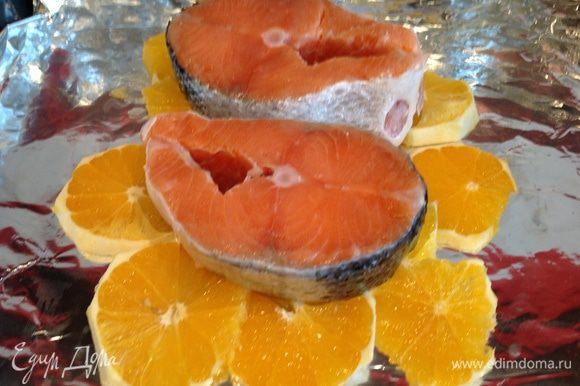 Выложите рыбу на апельсины, посолите.