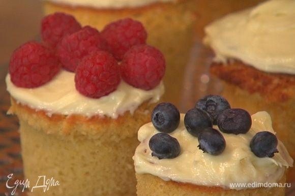 Готовые капкейки остудить, затем покрыть кремом и украсить ягодами.