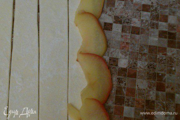 На полоску теста выложить 5-6 долек яблока, слегка внахлест. Дольки должны на одну треть выступать за верхний край теста. Аккуратно скрутить полоску в трубочку. Нижние края теста подвернуть вовнутрь.