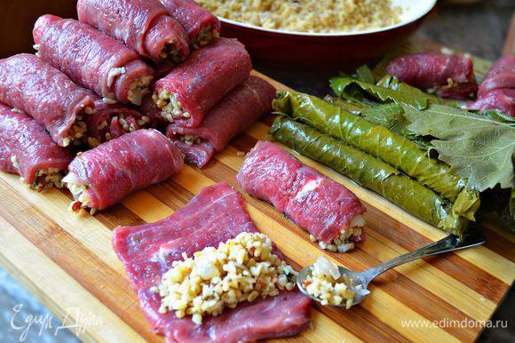 На каждый кусочек мяса укладываем подготовленную начинку, плотно сворачиваем. Большие рулетики можно разделить пополам. Затем каждый мясной рулетик заворачиваем в виноградный лист.