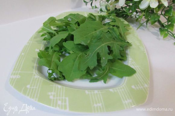 Руколу промыть и обсушить. Половину салата выложить на салатник.