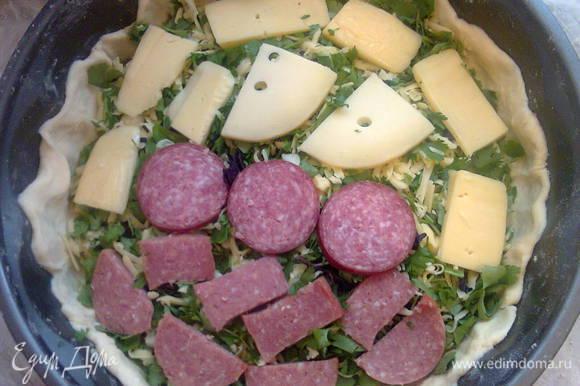На зелень положить нарезанный сыр и колбасу.