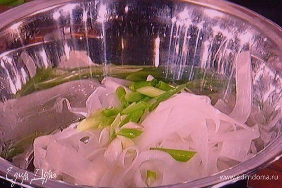 Для салата очистить дайкон и спец. ножичком для чистки овощей нарезать редьку на тонкие полоски. Добавить наискосок порезанный зелёный лук.