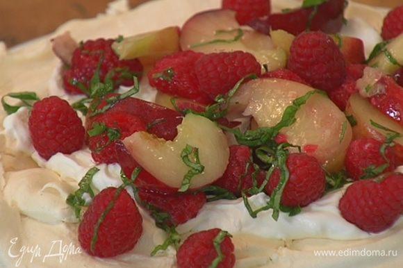 Остывшую меренгу переложить на тарелку, покрыть сливочным кремом, сверху разложить персики с малиной и базиликом и украсить все оставшейся малиной.