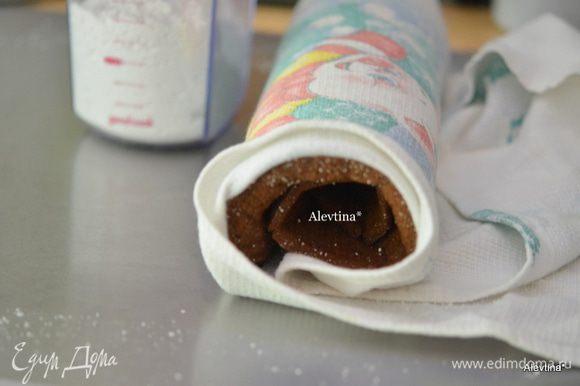 Готовый горячий бисквит выложить на полотенце с сахарной пудрой. Свернуть аккуратно и оставить так на несколько минут.