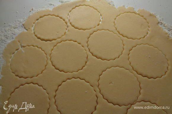 Отправим тесто в холодильник на полчаса. По истечении времени достанем его, разделим на 3 части. Каждую часть раскатаем на поверхности, присыпанной мукой. Если муки мало, то добавьте еще. Вырежем формочкой из теста кружочки.