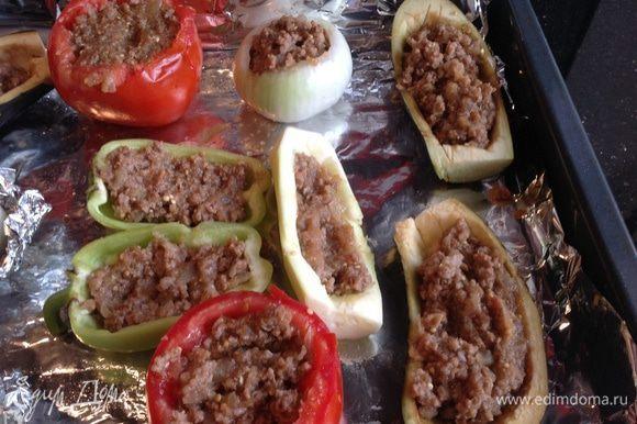Противень застелите фольгой, смажьте оставшимся маслом, выложите овощи. Заполните овощи фаршем. Готовьте в предварительно нагретой до 180 градусов духовке 25 минут.