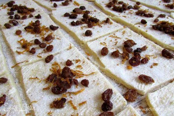 Через час, тесто еще раз вымесить. Рабочую поверхность присыпать мукой, раскатать тесто в пласт размером примерно 50х50см. Тесто смазать мягким сливочным маслом. Разрезать тесто на прямоугольники примерно 8х10см. Посыпать сахаром (5 ст. л.), сверху распределить смесь из изюма и апельсиновой цедры.