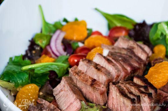 Для заправки смешаем оливковое масло, жидкость от мандаринов, соль и перец. Смешаем заправку с салатом, приготовленным заранее, а сверху красиво выложим тёплое мясо. Красиво и вкусно. Приятного аппетита!