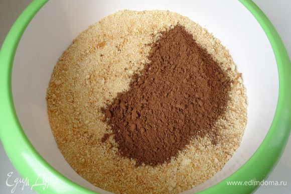 Для удобства приготовления шоколадной массы, бисквитную крошку высыпать в глубокую миску. Туда же всыпать какао и все хорошо перемешать до объединения.