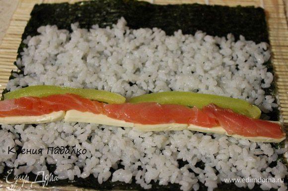 На середину риса выкладываем начинку, сыр, форель и перец.