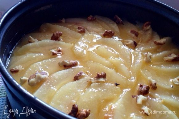 Сверху уложить груши, полить сверху грушевой карамелью и посыпать измельченными грецкими орехами. Выпекайте пирог в разогретой до 180°C духовке, 40 минут.