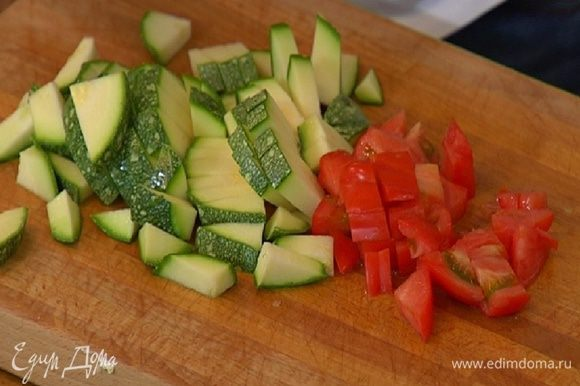 Цукини и помидор нарезать небольшими кубиками, добавить в суп и варить до готовности картофеля.