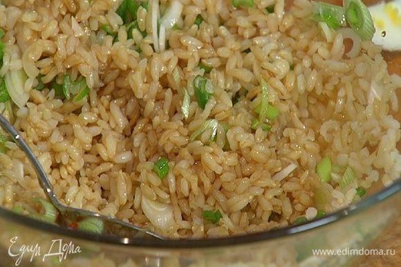 Готовый рис соединить с зеленым луком, полить оставшимся кунжутным маслом, рисовым уксусом, соевым соусом, посыпать подкопченным перцем чили и все перемешать.