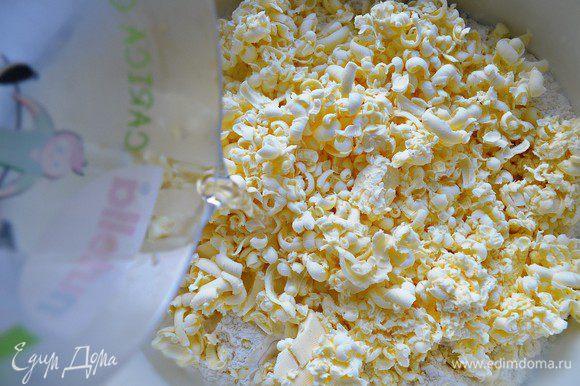Добавьте охлаждённое сливочное масло. Нарежьте его кубиками или натрите на тёрке. Смешайте масло с мукой до получения крошки. Добавьте ледяную воду.