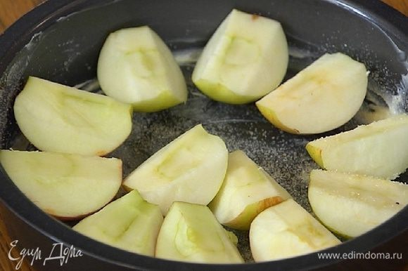 Форму для выпечки смазать оставшимся сливочным маслом, присыпать оставшимся сахаром, разложить яблоки срезами вверх, а сверху выложить тесто.