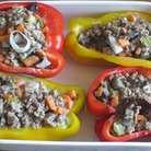 Половинки перцев заполнить фаршем, выложить в форму, влить бульон и запекать в разогретой до 200 ° С духовке 20 минут.