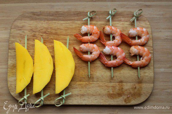 Манго очистить и нарезать ломтиками. Нанизать креветки и ломтики манго на шпажки.