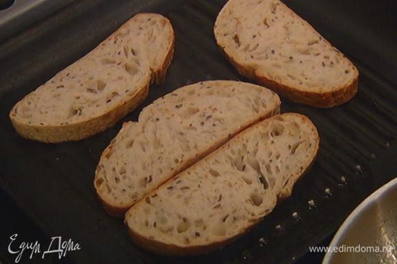Разогреть в сковороде-гриль 1 ч. ложку оливкового масла и обжарить хлеб с одной стороны.