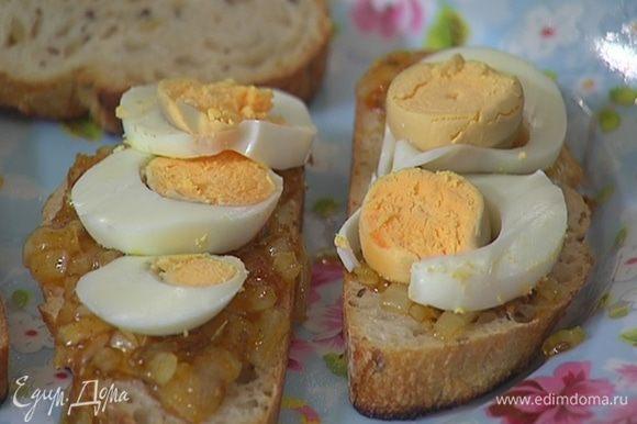 На гренки с соусом выложить нарезанные яйца, посыпать порванными руками листьями кинзы и накрыть гренками, намазанными маслом.