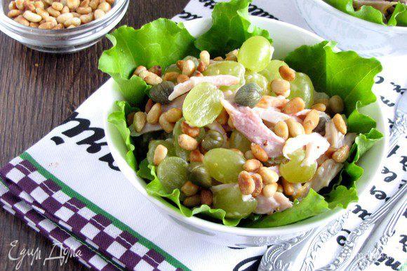 На дно салатника или тарелки положить салатные листы (подойдет любой листовой салат). Выложить приготовленный салат, полить заправкой и посыпать кедровыми орешками.