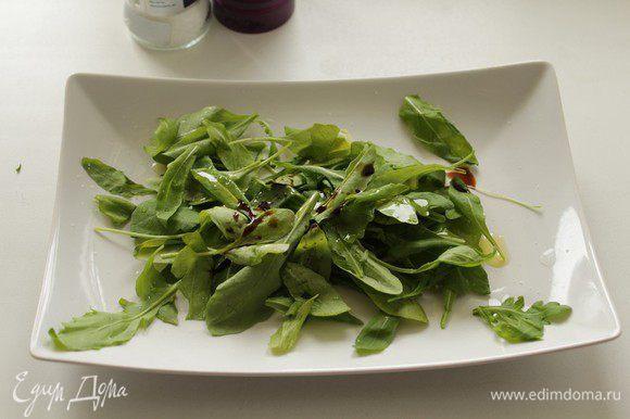 На блюдо кладем руколу, сбрызгиваем оливковым маслом и бальзамическим уксусом.
