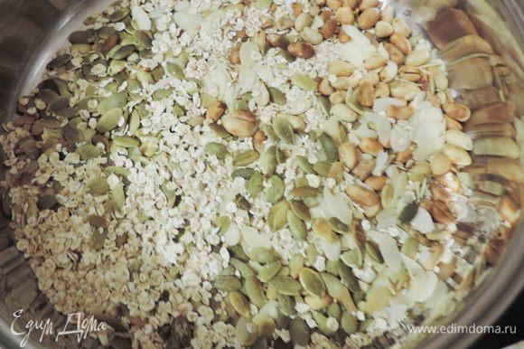Тем временем соединяем овсяные хлопья, семечки и орехи. Прокаливаем их на сковороде с толстым дном до появления легкого приятного запаха. Не пережгите!