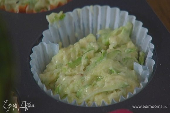 Формочки для маффинов выстелить бумажными вкладышами, смазать их оливковым маслом и разложить тесто.