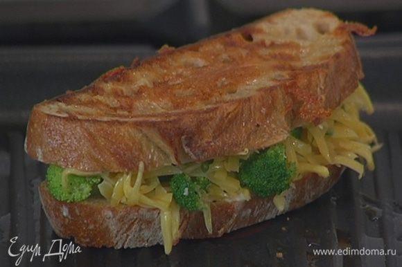 Разогреть в сковороде-гриль оливковое масло и, прижимая бутерброд к сковороде, обжаривать его с двух сторон до появления золотистых полосочек.