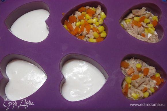 Достать из холодильника формочки и выложить кусочки куриного мяса, кукурузу и кубики моркови.