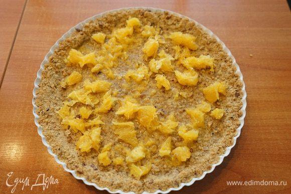 Теперь самое сложное: трём на мелкой терке цедру с двух апельсинов, откладываем на тарелку подсушиться. Очищаем апельсины от шкурки, пленок, перегородок и выкладываем порезанную мякоть на запеченную основу в форму.