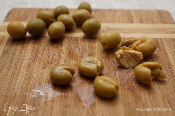 Плоской стороной ножа раздавить оливки, извлечь косточки и нарезать.