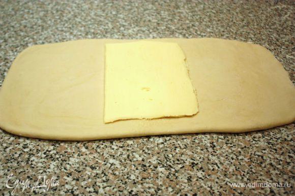 Тесто раскатать на присыпанной мукой поверхности в прямоугольник 23х46 см. Одну часть масляного блока положить на середину.