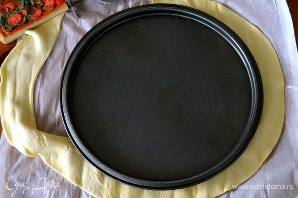 Теперь займемся нижним коржом. Один пласт слоеного теста раскатать и вырезать круг диаметром 26 см.